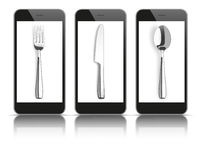 3 Black Smartphones Mirror Knife Fork Spoon. 3 black smartphones with knife, fork and spoon on the white background Royalty Free Stock Photos