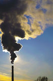 Black smoke against the blue sky and the Sun setting Royalty Free Stock Photography