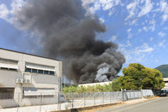 Black smoke from a blaze in a warehouse Royalty Free Stock Image