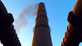 Black smoke from the chimney. By tube attached flues. Bottom view. The construction is illuminated by the setting sun stock video footage