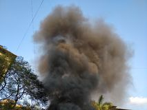 Black smoke coming out of a building on fire royalty free stock photo