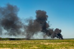 Black smoke in a green field. On blue sky stock photo