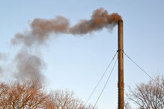 The black smoke from a pipe of a coal boiler room pollutes air. Stock Photography