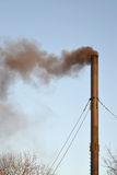 The black smoke from a pipe of a coal boiler room pollutes airutes air. Stock Images