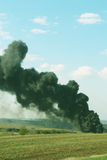 Black smoke rises, smoking and polluting - vertical photo. Volcanic eruption, harm ecology, fire emissions and chemical production waste, harmful industry stock image