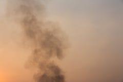 Black smoke on sunset sky background. royalty free stock photography