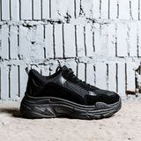 Black sneaker with thick soles on the cement floor against the background of brick wall royalty free stock photo