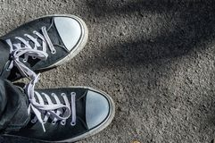 Black sneakers on a background of asphalt road stock photo