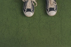 Black sneakers on a green welcome mat royalty free stock images