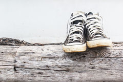 Black  sneakers on the old Log wood and gray concrete walls Stock Images