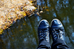Black sneakers shoes against water, nature Stock Photo
