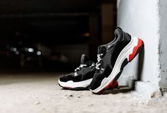 Black sneakers on a thick white sole with red inserts on a concrete background are supported on a white wall stock image