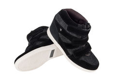 Black sneakers on a white background. Pair of black human sneakers on a white background royalty free stock images