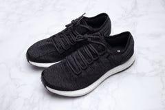 Black sneakers on white marble background Stock Photos