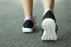 Black sneakers. On women`s legs Royalty Free Stock Photography