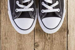 Black sneakers on wood background Stock Images