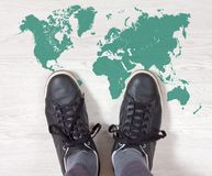 Black Sneakers on a World Map Outline Royalty Free Stock Photography