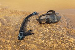 Black snorkel breathing tube and diving mask, in shallow sea on fine sand beach, sun shining on clear water stock photo