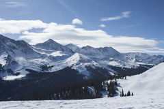 Black Snow Covered Mountain Ranges Under White Clouds and Blue Sky at Daytime Royalty Free Stock Photo