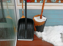 Black snow shovel standing in the snow leaning wall Stock Photos