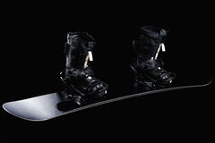 Black snowboard with black bindings and black boots. Isolated on black royalty free stock image