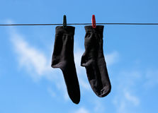Black socks hang drying on the clothesline with clothespins. Clo. Seup. On the background of blue sky with white clouds Royalty Free Stock Photos
