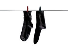 Black socks hang drying on the clothesline with clothespins. Clo. Seup. Isolated on a white background Royalty Free Stock Photo