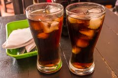 TWO GLASSES OF BLACK SODA AND ICE royalty free stock images