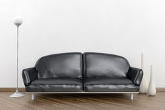 Black sofa in a white room Stock Images