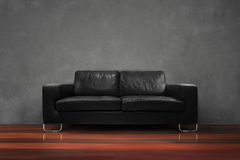 Black sofa with wooden floor concrete wall in empty living room. Lack sofa with wooden floor concrete wall in empty living room interior loft style Royalty Free Stock Photography