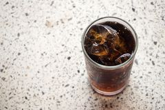 Black soft drink in glass. On marble floor. Favorite soft drink. Stock Photos