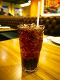 Black soft drink with ice and white suction tube, it is on the w Royalty Free Stock Images