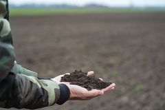 Black soil in man hands, farmer or agronomist holding black earth on spring field. The Black soil in man hands, farmer or agronomist holding black earth on royalty free stock photo