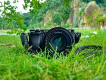 Black Sony Dslr Camera on Green Grass in Front of Brown and Green Mountain Royalty Free Stock Image