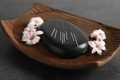 Black spa steen met reeks acupunctuurnaalden stock fotografie