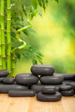 Black spa stones. On green bamboo background Stock Photography