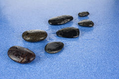 Black spa stones on blue background. Zen pebbles. Black spa stones on blue background Stock Photos