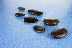 Black spa stones on blue background. Zen pebbles. Black spa stones on blue background Royalty Free Stock Photography
