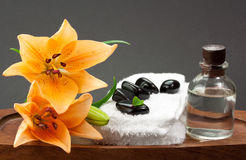 Black spa stones with flowers and essential oil Royalty Free Stock Photography