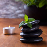 Black spa stones. With fresh mint, aromatherapy setting on wooden background Stock Image