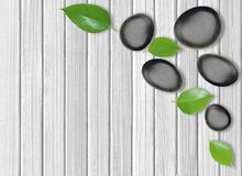 Black spa stones and green leaves on wooden Stock Images