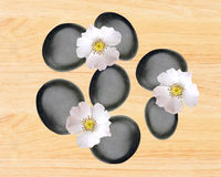 Black spa stones and white spring flowers over yellow wooden. Background Stock Image