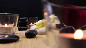 Black spa therapy stones surrounded by candles stock video