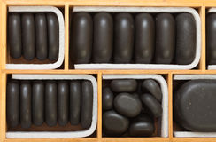 Black spa zen massage stones in wooden case as background Stock Image