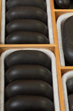 Black spa zen massage stones in wooden case as background Royalty Free Stock Photos