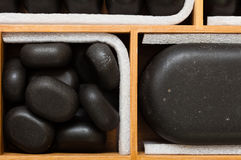 Black spa zen massage stones in wooden case as background Stock Images