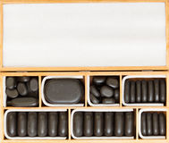 Black spa zen massage stones in wooden case blank copy space Royalty Free Stock Photo