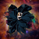 Black space queen. Beautiful woman in a fluttering dress flying in outer space. Fantastic art work. Elements of this image furnish Royalty Free Stock Photography