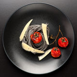 Black spaghetti with baked tomatoes and parmesan cheese Stock Images