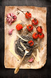 Black spaghetti with baked tomatoes and parmesan cheese Royalty Free Stock Images